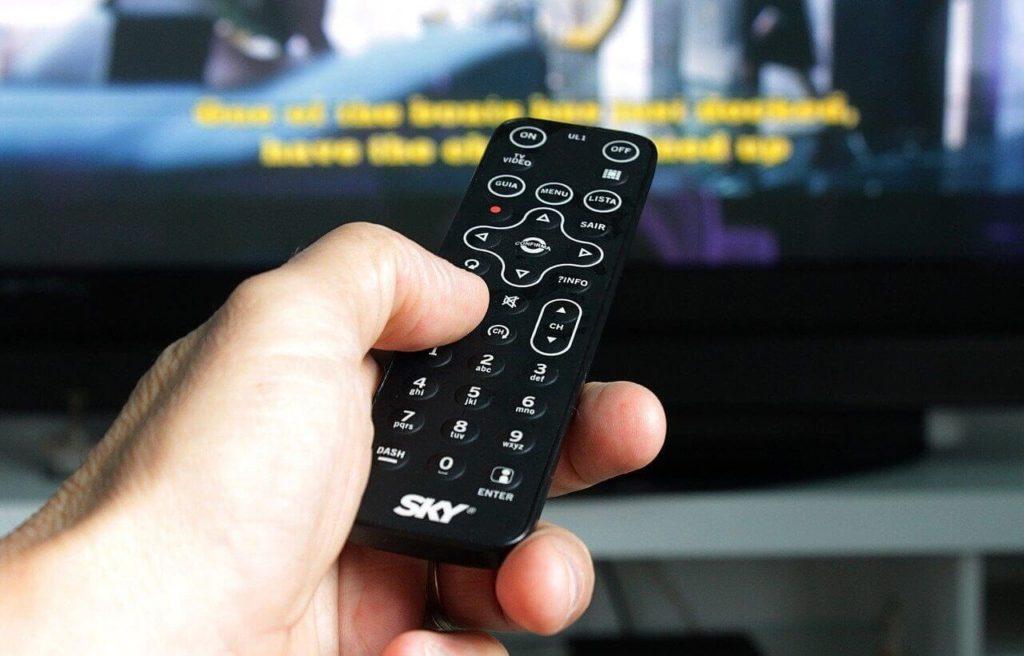 Um controle remoto da Sky apontando para uma TV desfocada ao fundo.