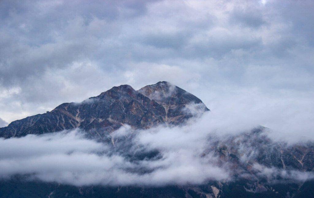 Uma montanha coberta por várias nuvens