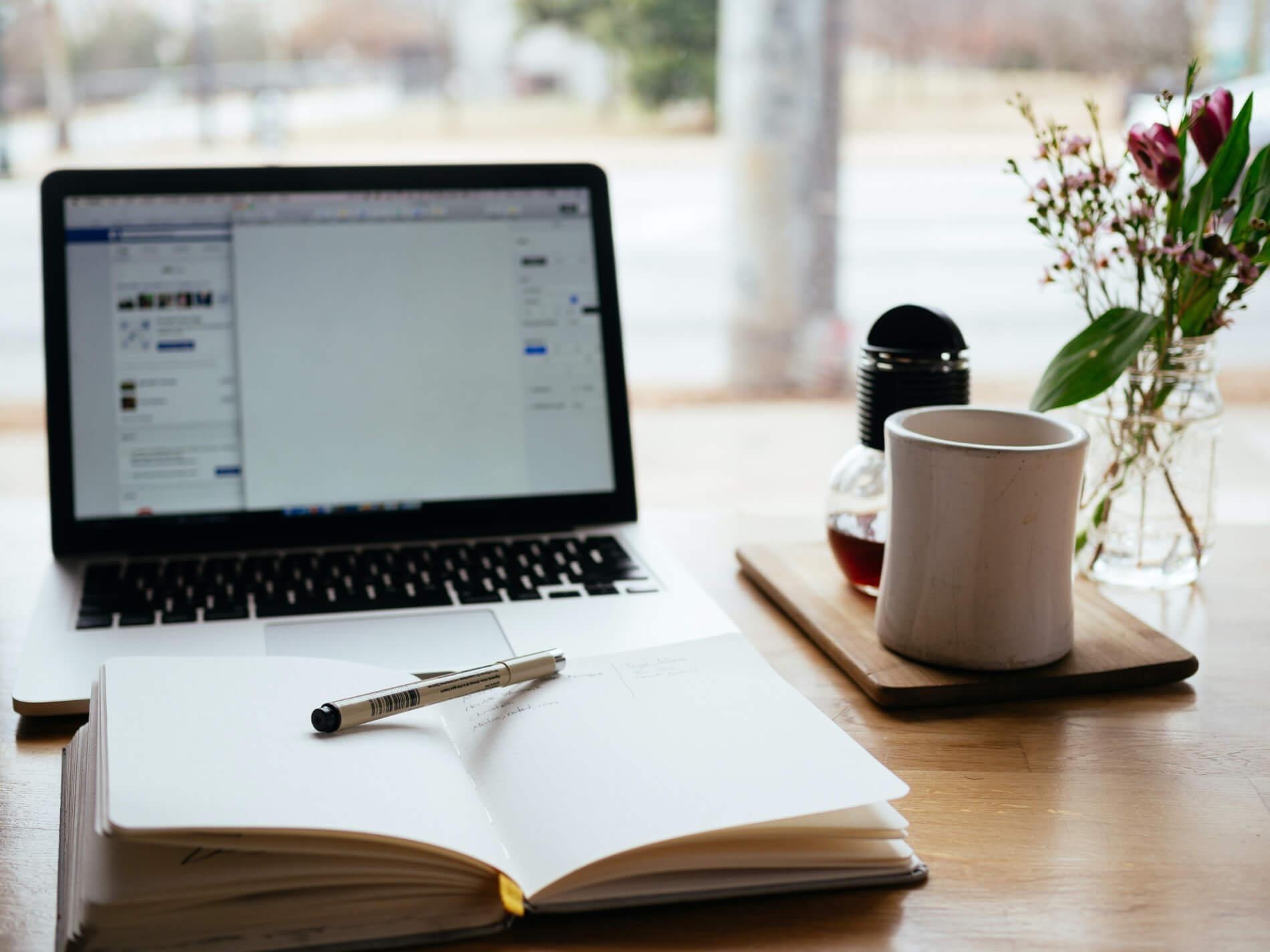 Um computador em cima de uma mesa com um bloco de anotações em sua frente com uma caneta em cima. Na direita, uma caneca e um pequeno vaso de plantas ao lado.