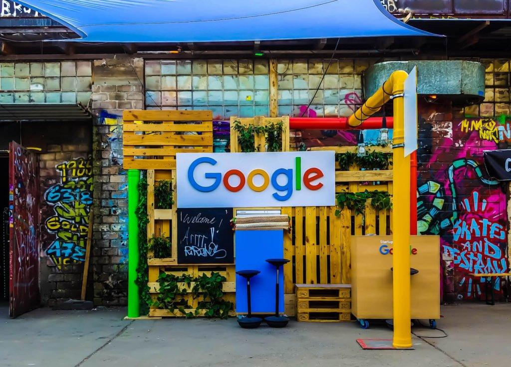 Um pequeno estande feito de pallets coloridos com uma placa com o logo do Google