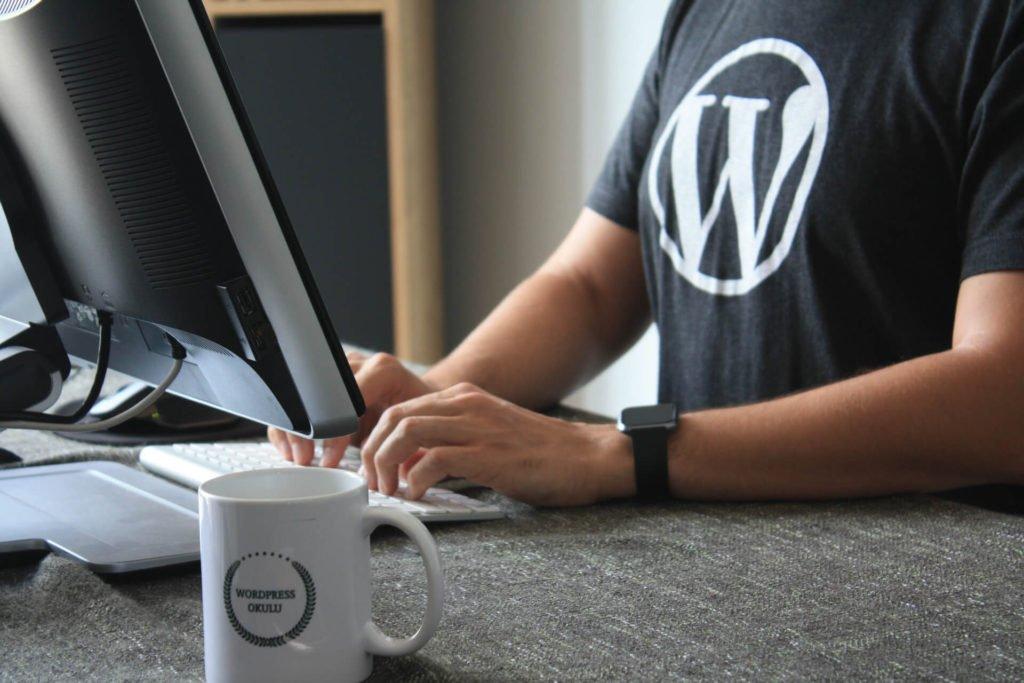 Um homem com uma camiseta do Wordpress digitando em um computador.