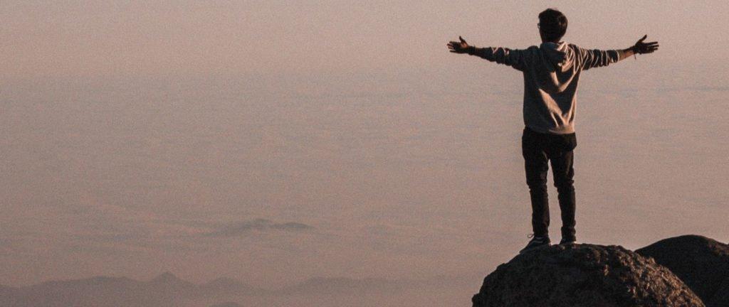 Um rapaz de braços abertos em cima de um morro olhando para o mar