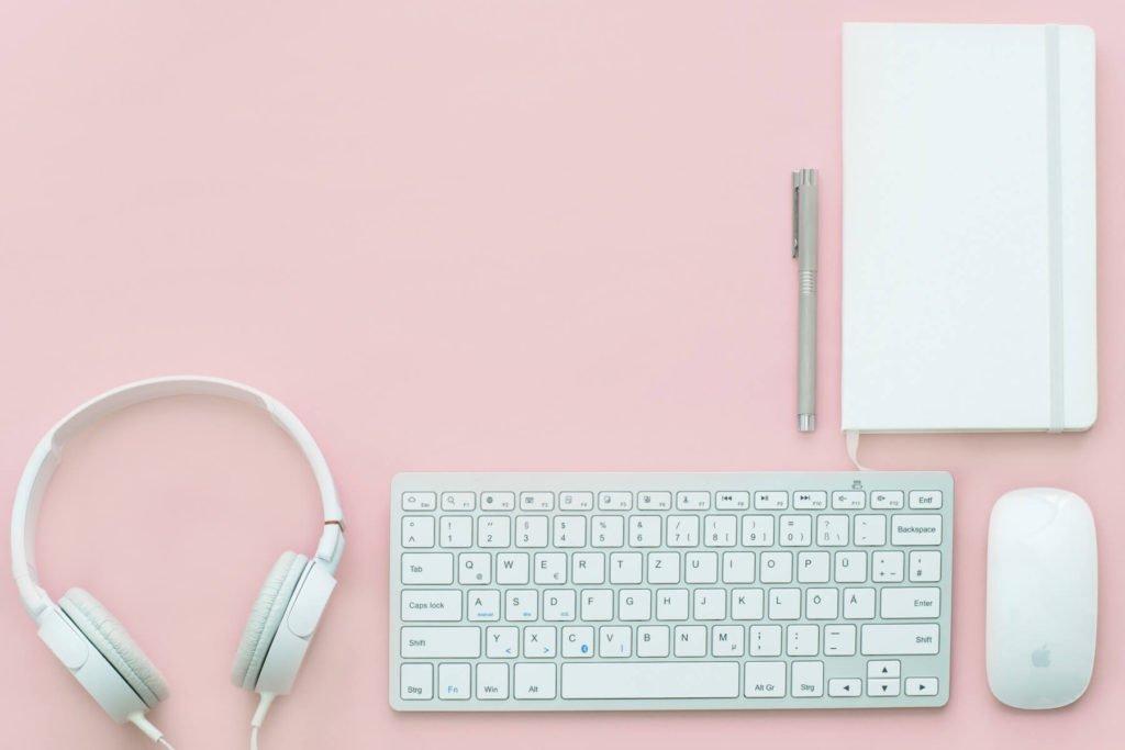 Um headphone, um teclado, um mouse, um caderno e uma caneta com um fundo rosa